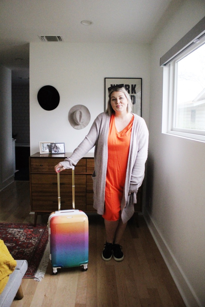 Sweater over coral dress and tennis shoes with luggage